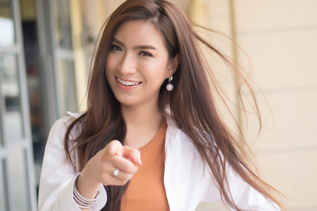 Happy smiling Asian Chinese woman pointing at you