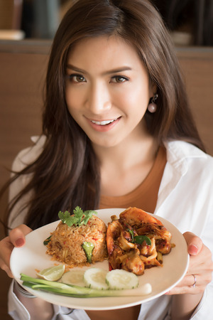 Asian Chinese woman enjoying spicy tomyum fried rice with prawn, spicy Thai seafood