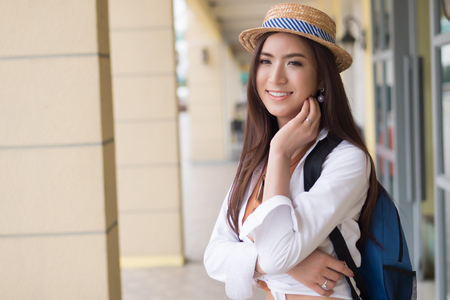 Happy Asian Chinese traveler smiling; portrait of Chinese Asian tourist with hat and backpack looking in European style building architecture; holiday, vacation, travel, tourism concept