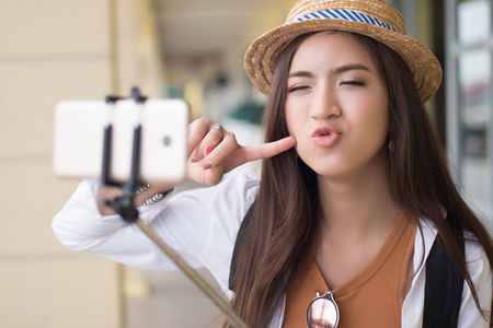 Happy Asian Chinese woman traveler taking selfie photo; portrait of happy smiling Chinese Asian woman tourist shooting self photograph with selfie stick; holiday, vacation, travel, tourism concept