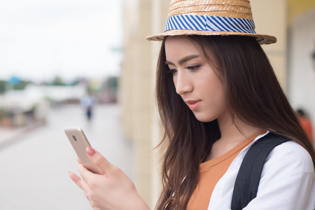Happy Asian Chinese woman traveler using smart phone; portrait of happy smiling Chinese Asian woman tourist using smartphone; communication technology, holiday, vacation, travel, tourism concept Stock Photo