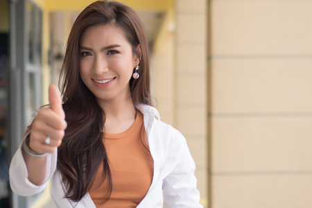 successful girl pointing thumb up; portrait of cheerful smiling woman pointing up approving, yes, ok, good, thumb up gesture; asian chinese woman young adult model