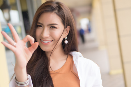 successful girl pointing ok hand sign; portrait of cheerful smiling woman pointing up approving, yes, ok, good, ok or okay gesture; asian chinese woman young adult model