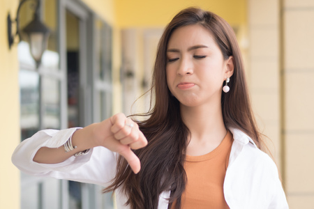 angry woman pointing thumb down; portrait of angry upset frustrated negative woman pointing up disapproval, no, bad, rejecting thumb down gesture; asian chinese woman young adult model