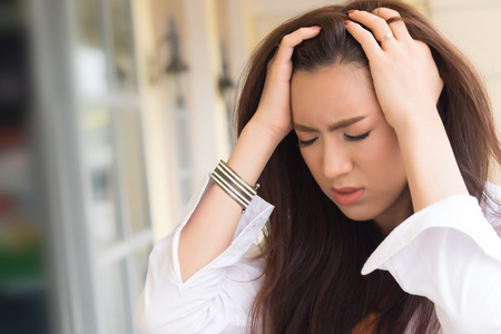 portrait of stressed sick woman with headache; ill woman suffers from vertigo, dizziness, migraine, hangover, health care concept; young adult asian woman model