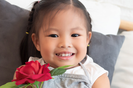 portrait of happy smiling positive asian child, cute little girl with love valentine rose