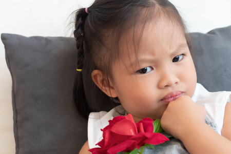 portrait of unhappy angry negative asian female child; cute little girl with love valentine rose Stockfoto