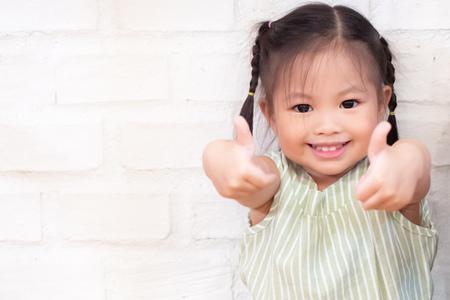 nettes kleines Mädchen, das Daumen aufgibt; Porträt des glücklichen, frohen, lächelnden positiven asiatischen Kindes.