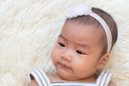 portrait of frowning little infant baby girl