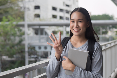 portrait of happy smiling asian woman college student pointing up 4 fingers, four points pose; winning, forth concept in city campus environment Stock Photo