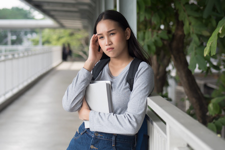portrait of stressed, serious, worried, upset asian woman college student thinking in city campus environment