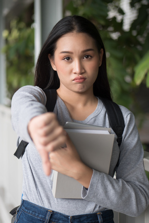 asian woman student pointing thumb down gesture; unaccepting, bad, no, rejection concept