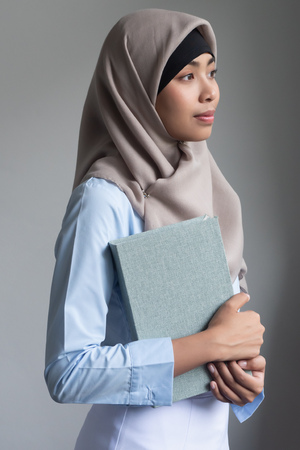 young adult asian muslim woman with the Quran, islamic holy book; concept of Ramadan, Eid al Fitr, meditation, islamic praying, islam religion education, muslim religious activities