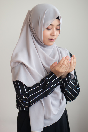 young modern asian muslim woman with islamic prayer hand; concept of Ramadan, Eid al Fitr, meditation, islamic praying, islam festival, muslim religious activities