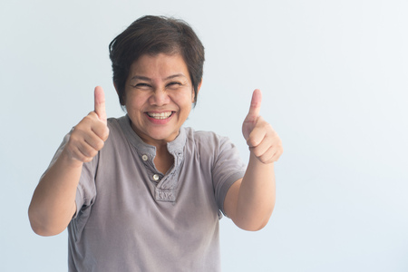 middle aged asian woman giving yes, ok, approving thumb up gesture Stock fotó