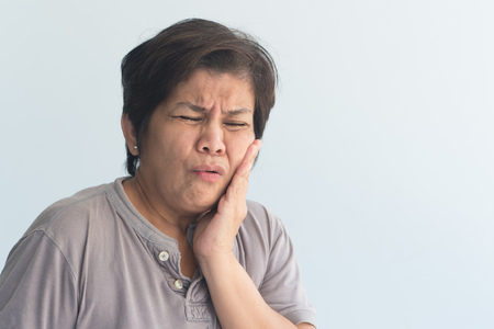 old senior woman suffering from toothache, tooth decay, tooth sensivity; oral health care concept Standard-Bild