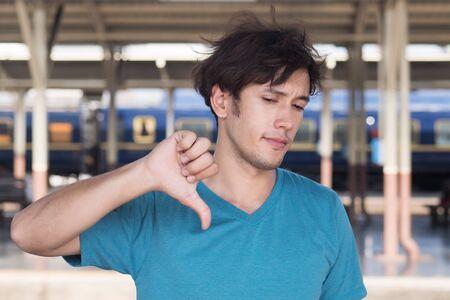 hombre apuntando con el pulgar hacia abajo signo de la mano; mal, incorrecto, abajo, rechazando, desaprobando concepto