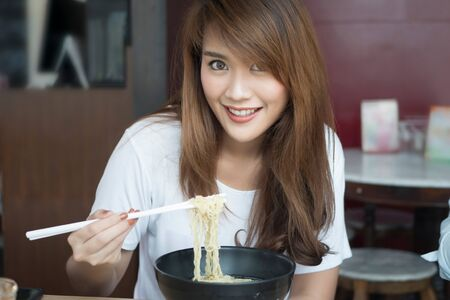 woman enjoying Chinese wonton or dumpling noodle with roasted duck