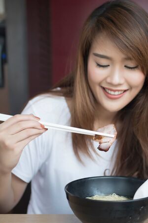 woman enjoying Chinese wonton or dumpling noodle with roasted bbq pork or Char Siu Stock Photo