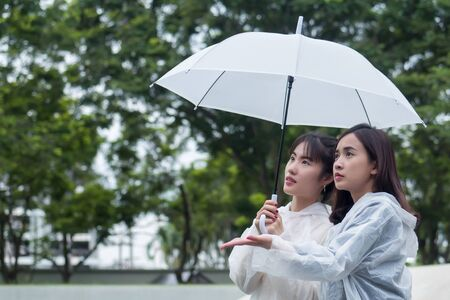 women with raincoat and umbrella in cloudy, overcast, rainy weather