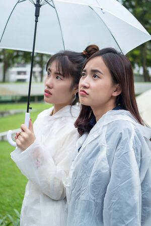 unhappy women with raincoat and umbrella in cloudy, overcast, rainy weather Stok Fotoğraf