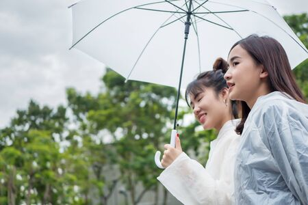 happy, relaxed women with raincoat and umbrella in cloudy, overcast day; pleasant rainy weather