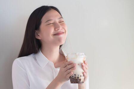 Happy smiling asian woman drinking iced bubble milk tea; aka boba tea, pearl milk tea, tapioca tea, asian exotic beverage concept