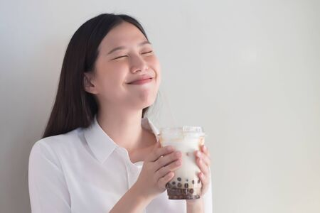 Happy smiling asian woman drinking iced bubble milk tea; aka boba tea, pearl milk tea, tapioca tea, asian exotic beverage concept