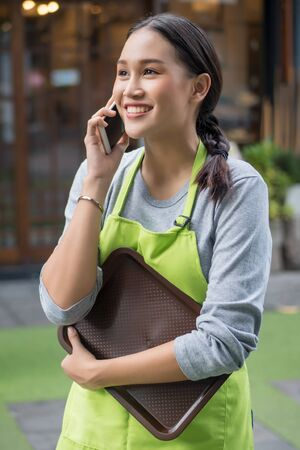 happy smiling small business owner, entrepreneur using smartphone