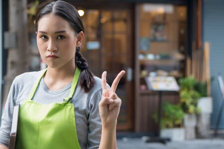 serious and determined woman entrepreneur, small business owner pointing up 2 fingers, v for victory sign