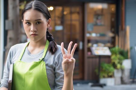 serious and determined woman entrepreneur, small business owner pointing up 3 fingers