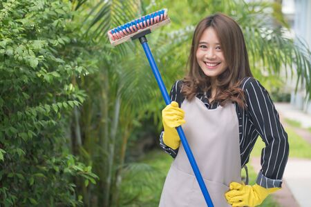 happy woman mopping the floor, doing housework, house keeping