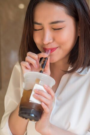 Happy smiling asian woman drinking iced bubble milk tea; aka boba tea, pearl milk tea, tapioca tea, asian exotic beverage concept; retouched image