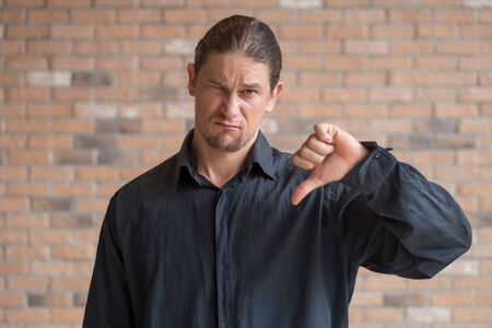 unhappy frustrated man showing thumb down gesture Stockfoto