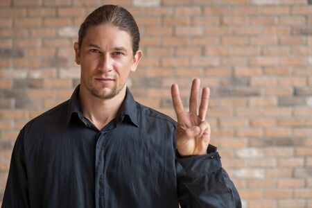 confident caucasian business man pointing up 3 fingers; concept of third place, three points