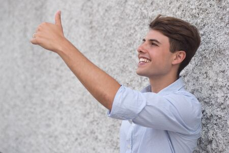 Happy smiling Hispanic man showing approving thumb up gesture Stockfoto