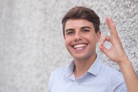 Happy smiling Hispanic man showing approving ok gesture