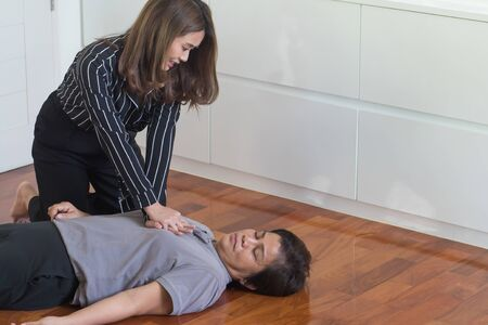 young woman doing CPR first aid to middle aged or senior unconscious woman; home first aid emergency rescue concept