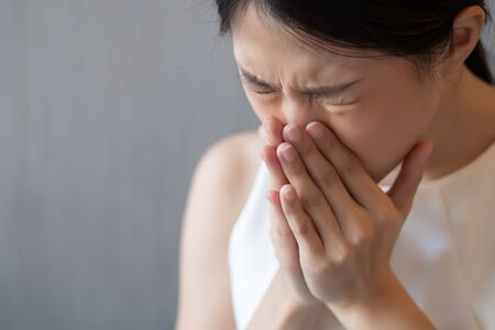 asian woman sneezing; concept of health care, body care, sickness, cold, flu, allergy, hay fever, rhinitis symptoms
