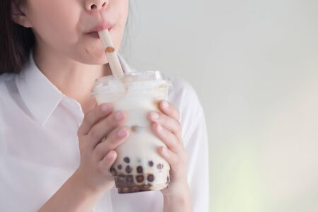 Asian woman drinking iced bubble milk tea; aka boba tea, pearl milk tea, tapioca tea, asian exotic beverage concept