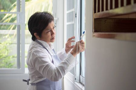 asian middle aged domestic helper woman cleaning windows, doing housework, housekeeping service Stock fotó