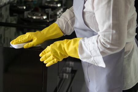 Aziatische huishoudster van middelbare leeftijd die de keuken schoonmaakt, huishoudelijk werk doet, schoonmaakserviceconcept