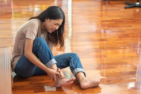 injured woman with ankle pain or foot injury; portrait of asian woman falling, having pain at her ankle; concept of wound, bruise, injury, pain from accident Reklamní fotografie