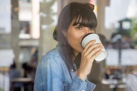 gelukkige Spaanse vrouw, Zuid-Amerikaanse Latijns-vrouw koffie drinken; concept van stedelijke levensstijl in coffeeshop Stockfoto