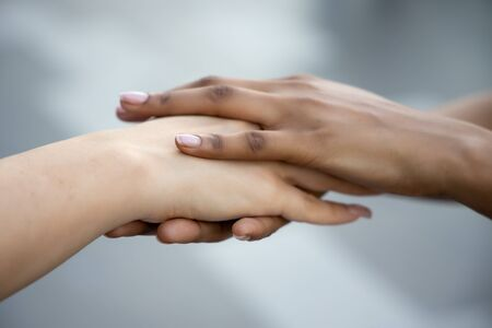 caucasian woman and african woman hand in hand, hand shaking to each other; concept of skin color tolerance, world peace, ethnicity understanding, team or teamwork