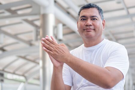 confident old senior man clapping his hand; strong happy healthy asian senior man in city environment; senior old man model for senior citizen, pensioner, retired man concept usage Foto de archivo