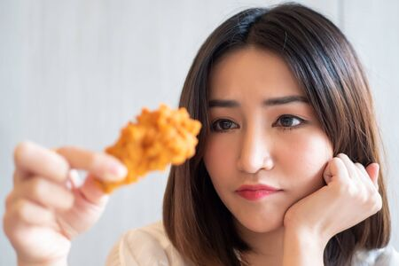 hungry worried woman looking and hesitating to eat fried chicken; concept of unhealthy delicious food, health care, unhealthy eating habit, fried chicken