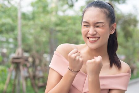 strong winning excited southeast asian woman face expression; portrait of strong successful positive excited happy smiling asian woman with successful exciting guts pose; asian adult woman model Stockfoto