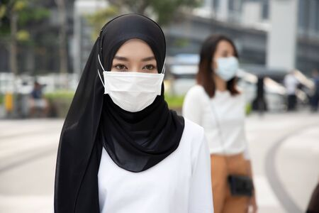 sick muslim woman wearing mask in city with dirty polluted smog; concept of global warming, dirty air, air pollution, allergy sickness, breathing difficulty, sore throat, lung cancer, bad air quality