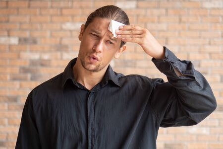 tired exhausted thirsty sweating man suffering from hot weather, heatstroke, high temperature; concept of climate change, global warming, heat stroke or heatstroke, sickness, body dehydration